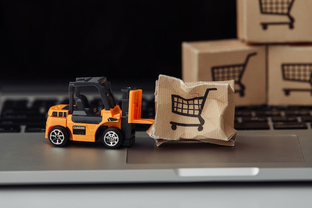 노트북에 지게차 모델 및 판지 상자. 택배 서비스 및 배송 사고 개념