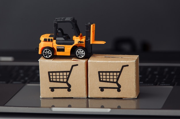 Forklift model on carton boxes on a laptop close-up
