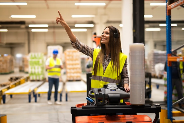 Forklift operator looking for an empty space on a shelf in warehouse distribution center