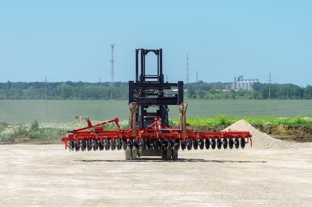 Вилочный погрузчик транспортирует дисковую борону. погрузчик едет по грунтовой площадке. транспортное оборудование.