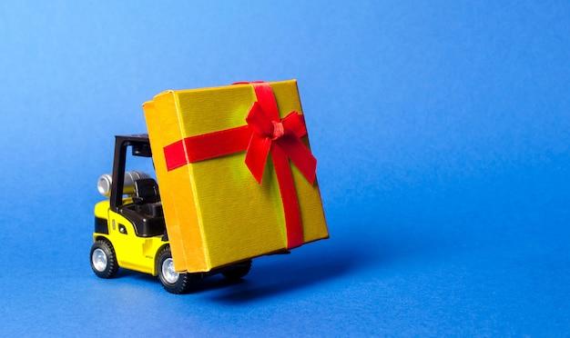フォークリフトは赤い蝶ネクタイが付いた金色の黄色のギフトボックスを運びますプレゼントの購入と配達