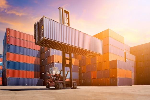 Автопогрузчик поднимая грузовой контейнер в судоремонтный