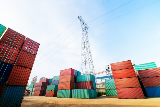 Forklift truck lifting cargo container in shipping yard.