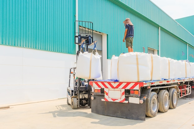Forklift truck with the sugar bulk bag on the truck pick up in distribution warehouse