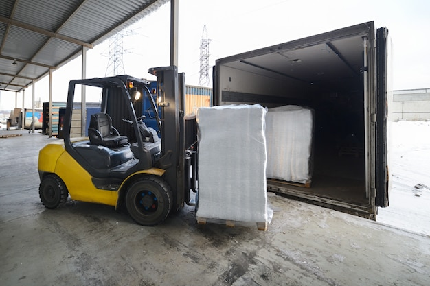 Forklift in warehouse loading box into a car outdoors