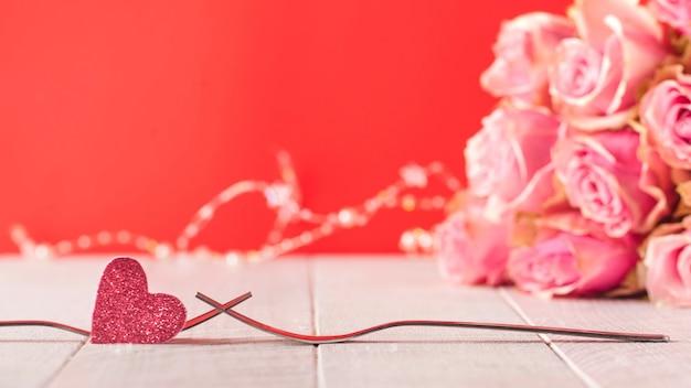 Вилки и сердечко на заднем плане букет роз праздничное меню на день святого валентина copy space