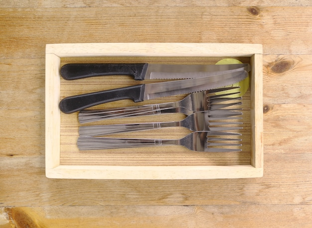 Forks and knifes in wooden tray