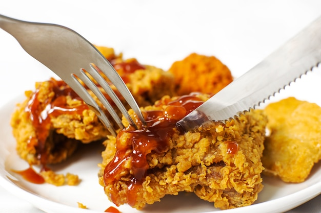 Forks and knives are shearing crispy chicken fried breast in a white plate topped with ketchup sauce.