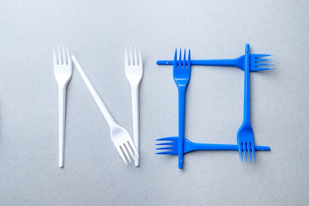 Forks made of plastic on a gray background laid out in the shape of the word no