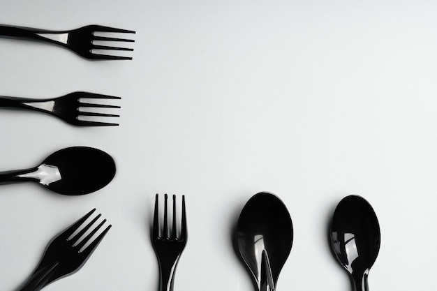 Forks and spoons on gray background. plastic cutlery, ecology, environmental pollution by plastic, disposable tableware, waste recycling concept. copyspace, flat lay.