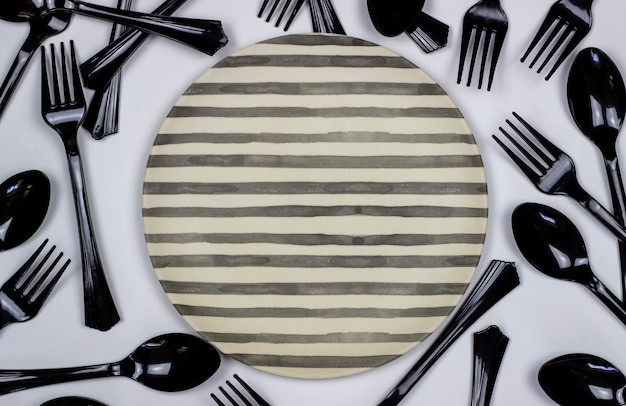 Forks and spoons next to the plate on white