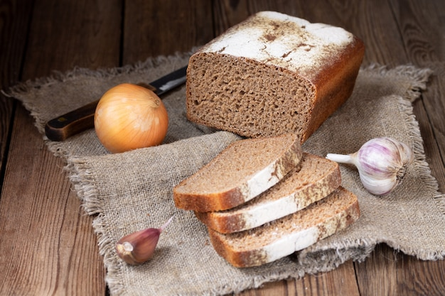 Form rye-wheat bread, sliced pieces, onions and garlic on a natural napkin.