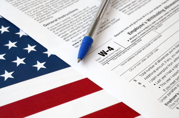 Form w-4 employee's withholding allowance certificate and blue pen on united states flag. internal revenue service tax form