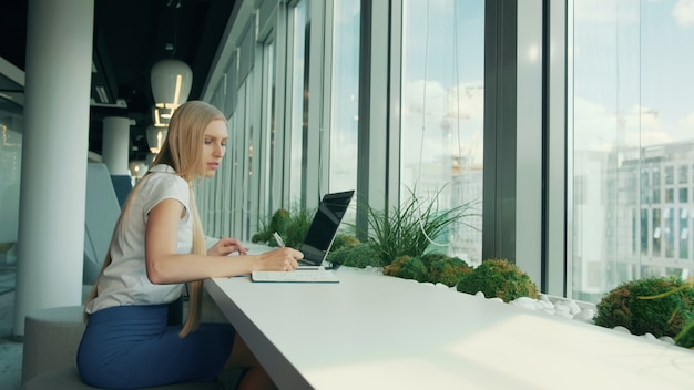 Formal woman with laptop and papers. side view of businesswoman writing on paper while sitting with laptop at table near window in modern office.