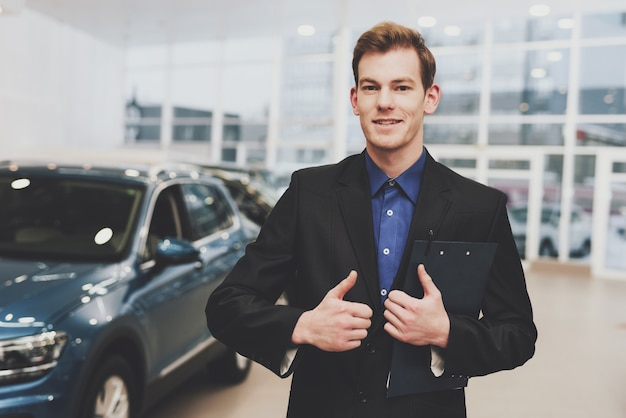 Formally dressed car dealer offers car credit