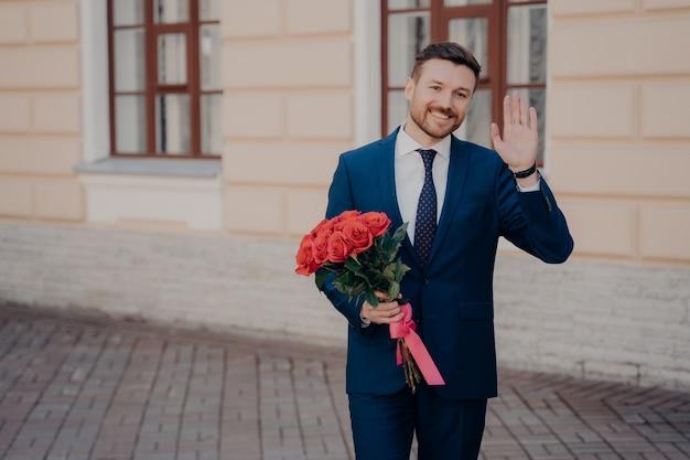 彼の特別な誰かに手を振って、笑顔で、赤いリボンで囲まれたバラの花束で愛する女性に挨拶し、屋外で一人で立っている青いスーツを着た正式な服を着た幸せな若い男