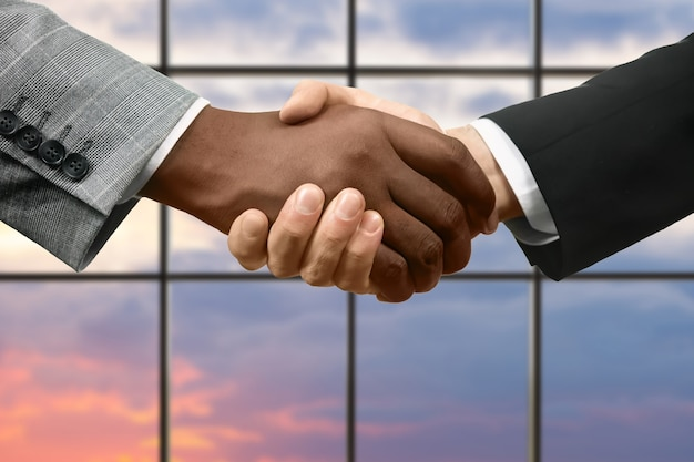 フォーマルな服装の男性が握手します。日没の背景にビジネス握手。真面目な人の合意。国家は友達になります。
