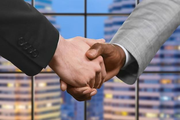 握手するフォーマルな服装の男性。幹部の夜の握手。国家の強い友情。企業間の合意。
