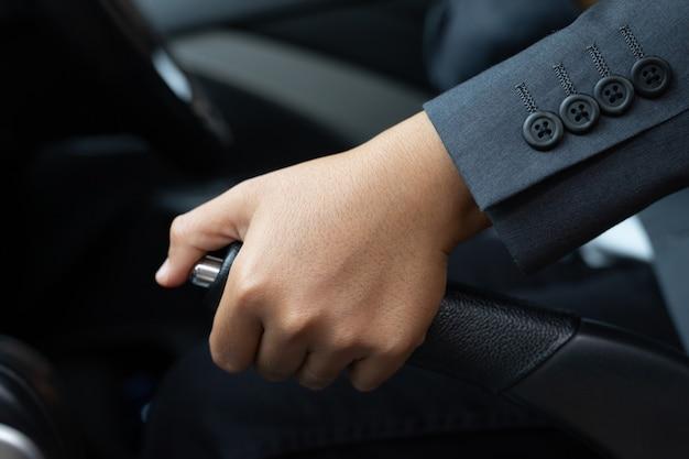 주차 중 핸드 브레이크를 당기는 정장을 입은 여성