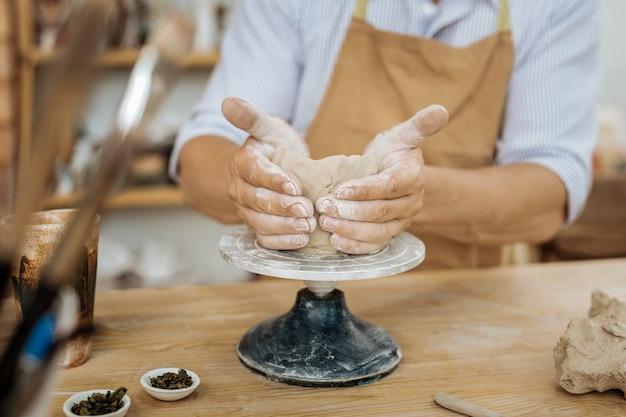 手で成形します。ろくろに手で花瓶を形成するプロの経験豊富な職人