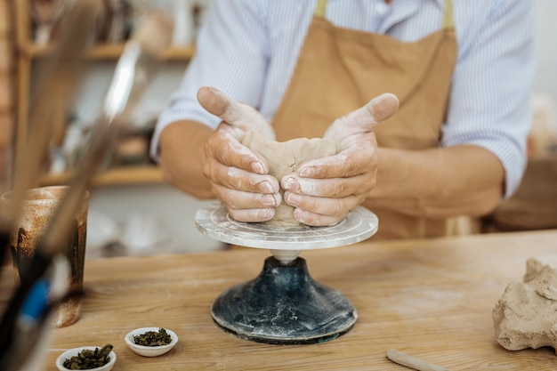 Forming with hands. professional experienced handicraftsman forming vase with his hands on pottery wheel