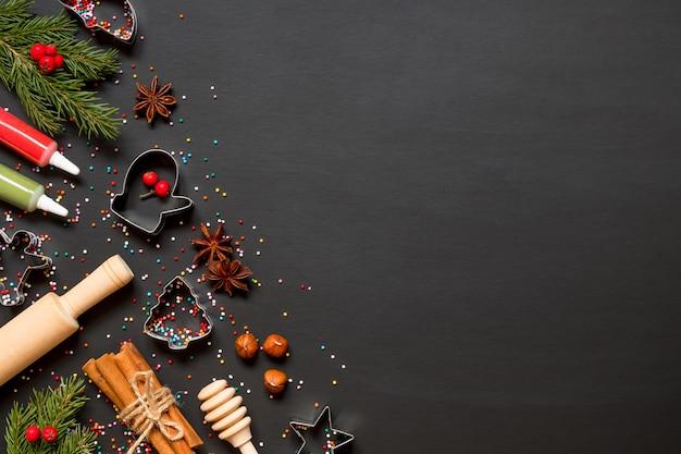 黒の背景にクリスマスクッキーを作るためのフォームと材料