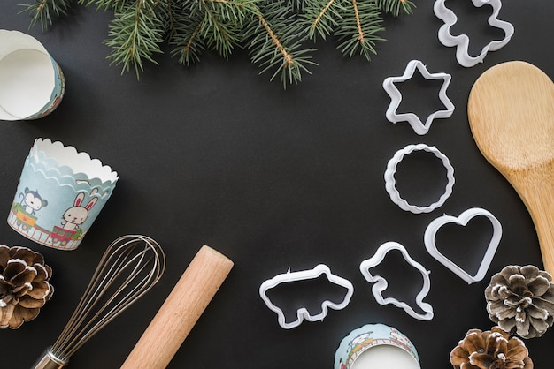 Forms for cookies near paper cups and fir twigs