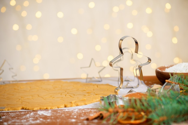 Forms for gingerbread christmas men and stars, close-up, top view, raw dough with cinnamon prepared for baking .