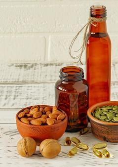 オメガまたは魚油サプリメットの形態-ゲルカプセル。木製のテーブルの上の液体オイルとナッツ。健康的なダイエット。