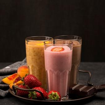 Fornt вид стаканов для молочного коктейля с фруктами и шоколадом
