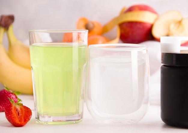 과일의 배경에 안경에 강화된 음료. 스포츠에 유용한 음료의 개념