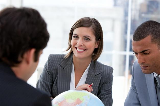 Fortunate businessteam looking at a terrestrial globe
