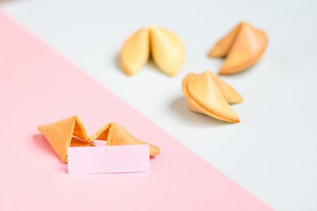 Fortune cookie on pink and blue background, pastel colors, copy space