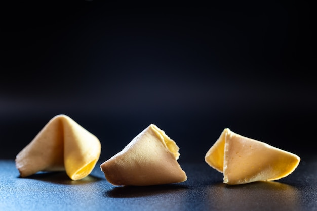 Fortune cookies on black background broken without message.