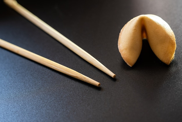 Fortune cookies on black background with chopsticks and copy space.