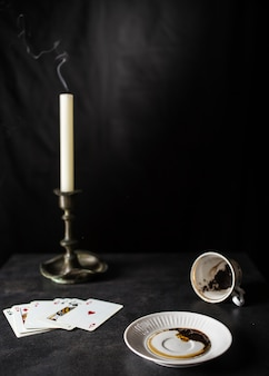Fortune teller reading coffee grounds in the state are near a deck of cards and a candle in the old candlestick