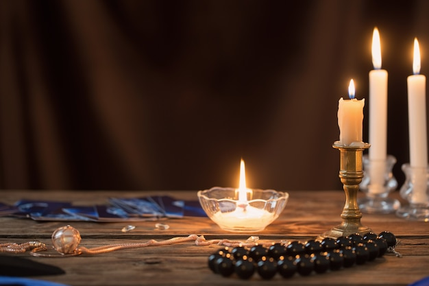 Fortune-telling cards and burning candles on a wooden table on  dark brown background