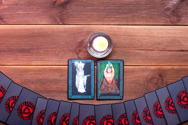 Fortune-telling cards on a wooden table with one candle with place for text. divination concept, tarot cards, psychic.