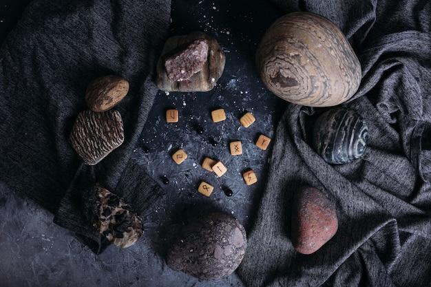 Гадание на деревянных рунах среди камней мрачного и загадочного стола ведьм