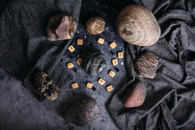 Гадание на деревянных рунах среди камней мрачного и загадочного стола ведьм Premium Фотографии