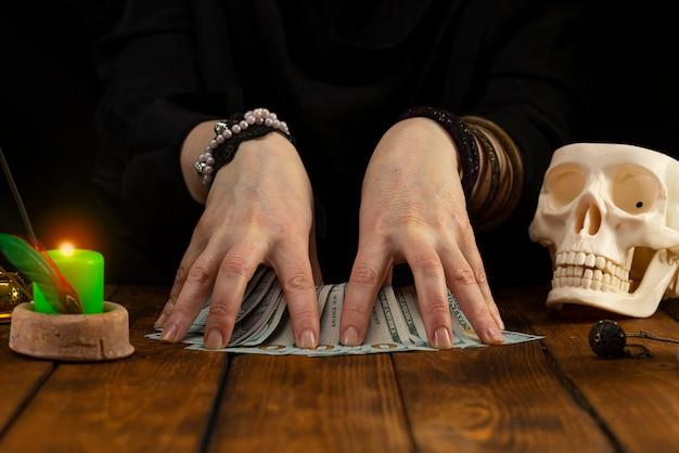 Fortuneteller's hands and divination cards on a wooden table