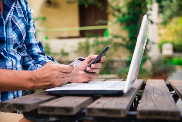 Forty years old caucasian man looking at credit card while working on laptop computer on garden terrace during sunny summer day. modern lifestyle - countryside weekend and shopping online concept.