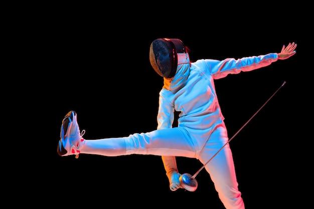 フォワード。黒い壁、ネオンの光で隔離の手に剣を持つフェンシングの衣装を着た十代の少女。動き、行動の練習とトレーニングの若いモデル。コピースペース。スポーツ、若者、健康的なライフスタイル。