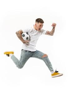 勝利に向けて。白い背景のスタジオでジャンプしてボールを蹴るサッカーサッカー選手としての若い男。サッカーファンと世界選手権のコンセプト。 s
