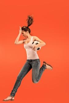 앞으로 승리를 향해. 점프 하 고 빨간색 배경에 스튜디오에서 공을 차는 축구 축구 선수로 젊은 여자. 축구 팬과 세계 선수권 대회 개념. 인간의 감정 개념