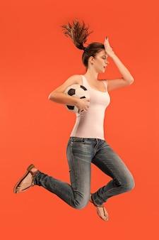 勝利に向けて。サッカーのサッカー選手としての若い女性がジャンプしてボールを蹴る