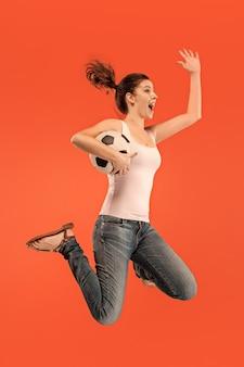 勝利に向けて。サッカーサッカー選手としての若い女性が赤でジャンプしてボールを蹴る