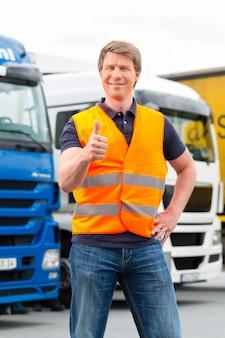 Экспедитор или водитель перед грузовиками в депо Premium Фотографии