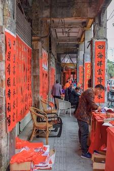 Фошань, провинция гуандун, китай. 8 февраля 2021 года. каллиграф пишет для людей куплеты весеннего фестиваля. это самый распространенный и важный обычай празднования китайского нового года.