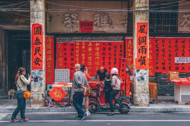 Фошань, провинция гуандун, китай. 8 февраля 2021 года. люди пишут куплеты с поздравлением с праздником весны. подготовка к празднованию китайского нового года на улице куаизи в фошане